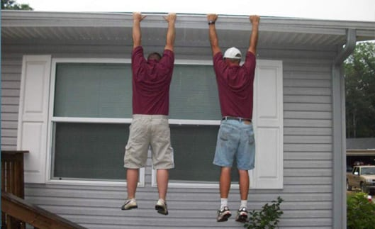 Two men hanging from strong seamless gutters